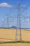 High voltage lines and power pylons in a green agricultural landscape on a sunny day with cirrus clouds in the blue sky. Stock Photo