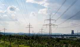 High voltage lines and power pylons in a green landscape, gray sky and chimney of a nuclear power plant in the background. High voltage lines and power pylons stock images