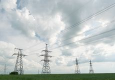 High voltage lines and power pylons and a green agricultural landscape on a sunny day. High voltage lines and pylons and a green agricultural landscape on a stock photos