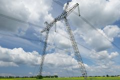High voltage lines and power pylons and a green agricultural landscape on a sunny day. High voltage lines and pylons and a green agricultural landscape on a royalty free stock photo