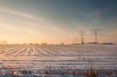 High voltage lines and pylons in a snowy stubble field Stock Photography