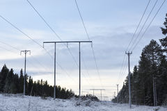 High-voltage lines. Three pararell high-voltage lines against a cloudy sky,picture from the North of Sweden Royalty Free Stock Photo