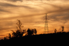 High voltage pole with golden sky. High voltage pole on mountain with golden sky Royalty Free Stock Photo