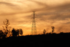 High voltage pole with golden sky. High voltage pole on mountain with twilight Stock Photo