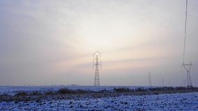 High voltage pole illuminated by a sun hidden in the mist stock image
