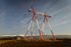 High Voltage Pole. Red and white high voltage tower in the middle of plowed field. Warm late afternoon sunlight, with snowy mountains in background and blue sky royalty free stock images