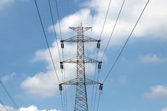 High voltage pole and voltage power line on blue sky background. royalty free stock images