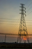 High voltage poles. High voltage power pylons in the field with sunset Stock Photo