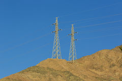 High-voltage poles with wires. In the mountains Royalty Free Stock Images