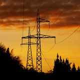 High voltage polls. Profiled over a beautiful orange sunset Stock Photo