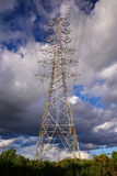 high voltage post against blue sky Stock Images