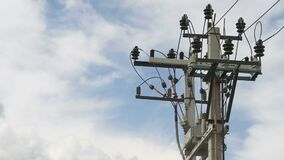 High-voltage electric line outdoors. Close-up. High-voltage post on the background of blue sky with white clouds. High-voltage electric line. Electricity stock video footage