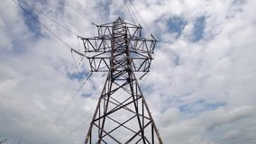 High voltage post. High-voltage tower sky background. High-voltage electrical insulator electric line against the blue sky. Electricity transmission power lines stock video footage