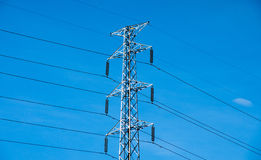 High voltage post or power transmission line tower and blue sky Stock Image