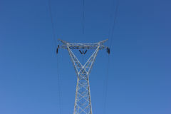 High voltage post, power transmission tower against blue sky royalty free stock image