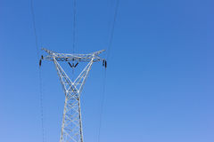 High voltage post, power transmission tower against blue sky.  royalty free stock photography