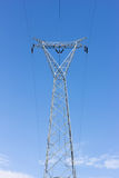 High voltage post, power transmission tower against blue sky royalty free stock images