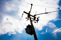 High voltage post with sunny blue sky. High voltage tower with sky in the background. Electric power concept with power lines and. High voltage post with sunny Royalty Free Stock Photography