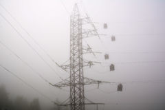 High voltage post tower on foggy early morning background Stock Photos