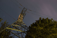 High voltage post or tower up view with tree and night sky clouds. Long exposure photography Stock Photos