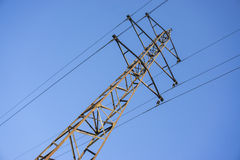 High voltage power grid pylon against blue sky Stock Images