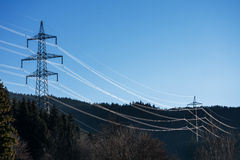 High voltage power line across the forest Royalty Free Stock Image