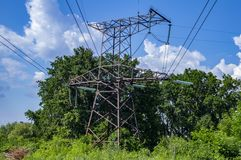 High-voltage power line against the blue sky with clouds royalty free stock image