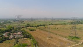 High voltage power line. Electricity pylons bearing power supply across agricultural land with sown green, rice fields in countryside. aerial view power pylons royalty free stock photos