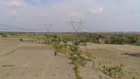High voltage power line. Electricity pylons bearing power supply across rural landscape. aerial view power pylons and high voltage lines java, indonesia.High stock video