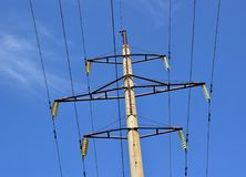 High-voltage power line. A fragment of a power line. The vertical position of the image. Blue sky Royalty Free Stock Photo