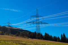 High-voltage power line on the hillside. High-voltage power line on the mountainside on blue sky background royalty free stock image