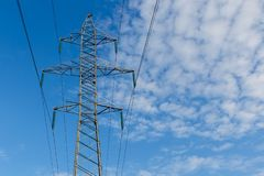 High voltage power line on metal poles. Power lines on metal pillars against a blue sky with clouds, high voltage power line royalty free stock image