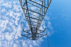 High voltage power line on metal poles. Power lines on metal pillars against a blue sky with clouds, bottom view stock image