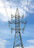 High-voltage power line metal prop over cloudy blue sky Royalty Free Stock Images