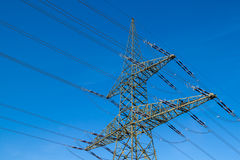 High-voltage power line. A high voltage power pylons against blue sky royalty free stock photos