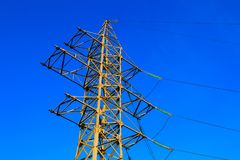 High voltage power line and sky. High-voltage electric tower and power lines they conducting electrical energy against the blue sky and rays of the setting sun Stock Photography