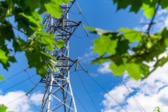 High voltage power line and sky. High voltage electricity pylon and transmission power line on the blue sky and white clouds on the background. A look through Royalty Free Stock Images