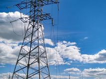 High voltage power line and sky. High voltage electricity pylon and transmission power line on the blue sky and white clouds on the background Royalty Free Stock Photography