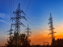 High voltage power line and sky. Silhouettes of high-voltage electric pylons and power lines against the background of the setting sun Stock Photography