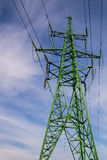High voltage power line stand. Green stand blue sky with clouds Royalty Free Stock Photos