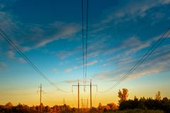 High - voltage power line. Wires and power towers of electricity. Above the forest at sunset. Supply of energy Stock Image