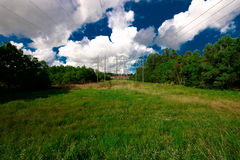 High voltage power lines. With blue sky and clouds overhead Royalty Free Stock Photo