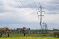 High voltage power lines above spring meadow. Electricity poles stock photography