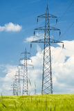 High voltage power lines against a blue sky Royalty Free Stock Photo