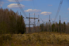 High voltage power lines against the blue sky. And the spring forest Royalty Free Stock Photography