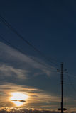High voltage power lines on colorful sky background at sunset. Stock Images