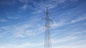 High voltage power lines and electricity pylon on cloudy sky background, Time lapse stock video