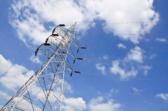 High voltage power lines with electricity pylons at blue sky. Royalty Free Stock Photo