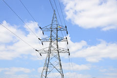 High voltage power lines with electricity pylons at blue sky. Royalty Free Stock Photography