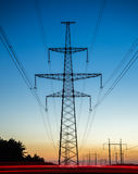 High voltage power lines with electricity pylons at twilight Royalty Free Stock Photography